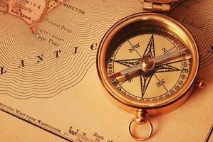 foto van een oud koperen kompas over een kaart