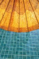 gele papieren paraplu bij zwembad verticaal foto