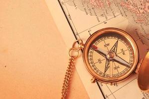 antiek koperen kompas over oude kaart foto