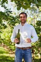 man met een glas witte wijn in de wijngaard foto