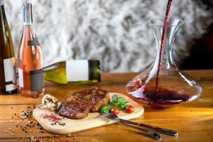 grote varkenssteak met kruiden, tomaten en flessen wijn foto