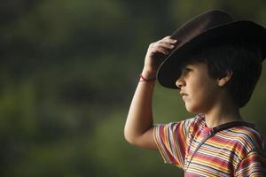 jongen die avonturiershoed neemt die naar het landschap kijkt.