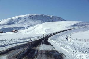 besneeuwde en gladde weg met vulkanische bergen in de winter