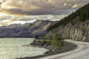 gebogen asfaltweg in hoge bergen van alaska