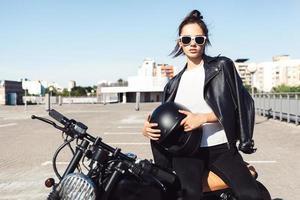 biker meisje zittend op vintage aangepaste motorfiets