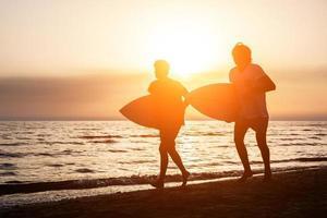 twee jongens met surfplanken bij zonsondergang