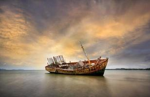 vintage visser, bootwrak zonsonderganglicht op het strand.