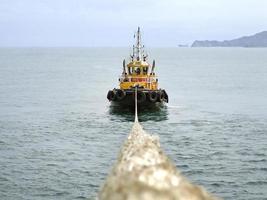sleepboot trekt een schip in de haven