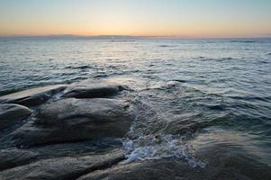 rotsachtige kust met golven bij zonsondergang foto