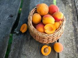abrikozen in een mand op houten achtergrond foto