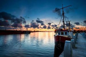 vissersschepen bij zonsondergang in zoutkamp