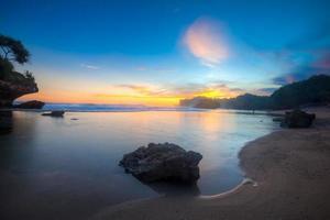 zonsondergang op het strand van kukup indonesië foto