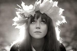 portret van een vrouw die een krans van esdoornbladeren draagt