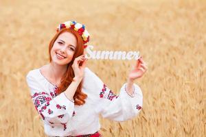 roodharige meisje in nationale Oekraïense kleding met houten woord summ