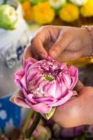 vrouw die bloemblaadje roze lotusbloem vouwt voor bid Boeddha in het Thais