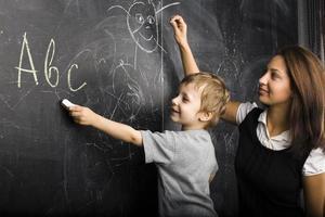 kleine schattige jongen in de klas met leraar foto