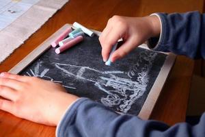 kind tekenen op een schoolbord foto