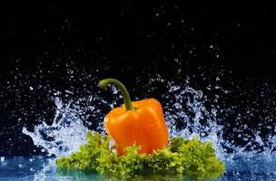 peper in spray van water. sappige peper met plons foto