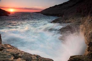 golven breken op een rotsachtige kust bij zonsondergang