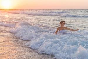 jonge bruid geniet van een toevallig bad in het oceaanwater.