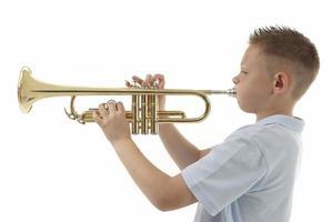jongen speelt trompet foto