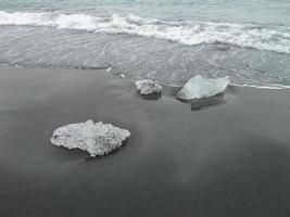 strand met stukjes ijs