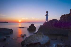 jonge mooie vrouw ontspannen op rotsachtige kust?