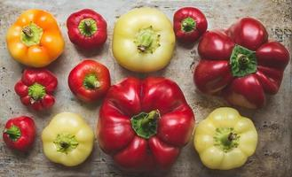 zoete paprika van verschillende grootte en kleur op een rustiek foto