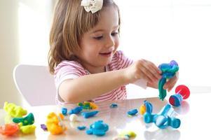 een gelukkig jong meisje dat verschillende kleuren speldeeg mengt foto