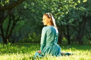 vrouw in jurk onder appelbloesems foto