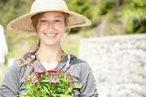 tuinierende dame met een zonnehoed foto