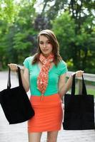 mooi meisje met doek boodschappentassen lopen op houten brug foto