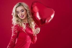 grote rode hartvormige ballon vastgehouden door vrolijke vrouw foto