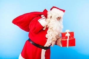 Kerstman met geschenken op handen op blauwe achtergrond foto
