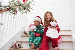 twee kinderen zitten op trappen in pyjama's met kerstmis foto