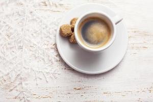 kopje koffie, sneeuwvlok op witte houten achtergrond foto