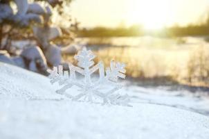 decoratieve sneeuwvlok op sneeuw bij zonsondergang
