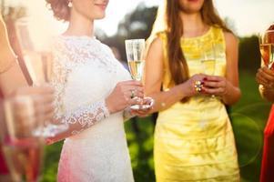 bruid met bruidsmeisjes roosteren foto