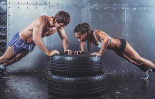 sporters. fit sportieve vrouw en man doen push-ups op foto