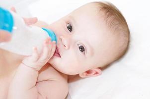 leuke baby eet uit klein flesje foto
