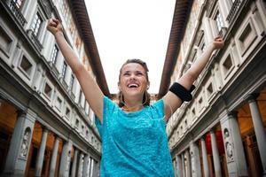 gelukkige fitness vrouw die zich verheugt in de buurt van uffizi-galerie in florence