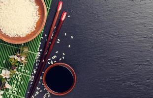 Japanse sushi-eetstokjes, sojasauskom, rijst en sakurabloesem foto