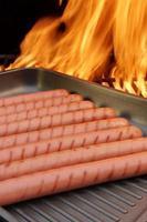 gegrilde worstjes op koekenpan en bbq-grill op achtergrond