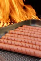 braadworsten op grillpan en bbq-grill op achtergrond