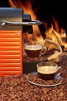 capsule koffiemachine met twee espressokopjes bij open haard foto