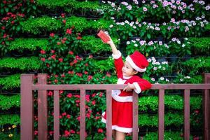 klein Aziatisch meisje in rood kerstman kostuum met huidige doos in het park foto