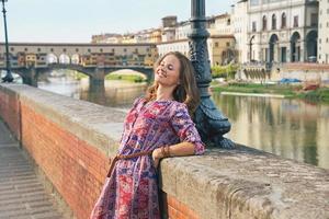 jonge vrouw aan de kade in de buurt van de ponte vecchio in florence, italië