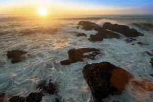 oceaan surfen op de rotsen tijdens geweldige zonsondergang.