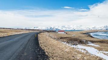 asfaltweg met berg in husavik, ijsland