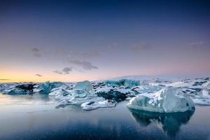 ijsbergen die in jokulsarlon gletsjermeer drijven bij zonsondergang. zuid-ijsland. foto